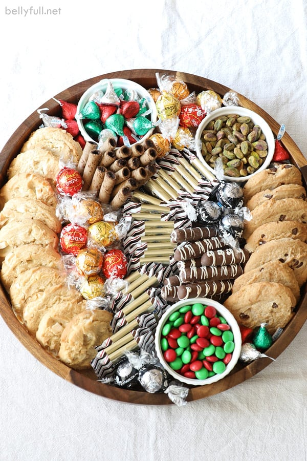 round charcuterie board filled with cookies, truffles, and chocolate with red and green for Christmas