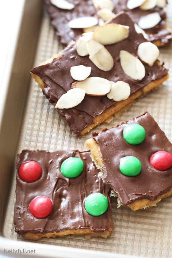 broken up pieces of Saltine Cracker Toffee topped with sliced almonds and red and green M&Ms