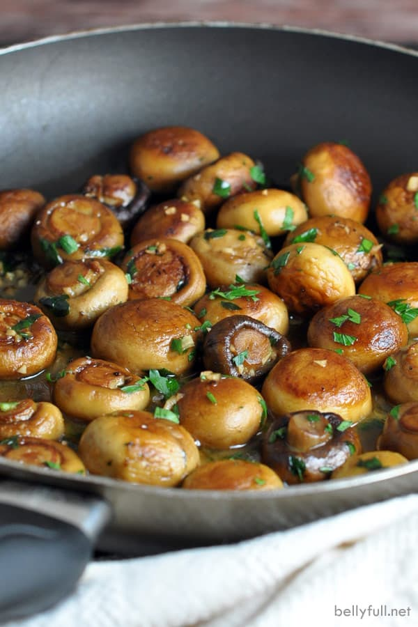 whole sauteed mushrooms in a pan covered in butter garlic sauce