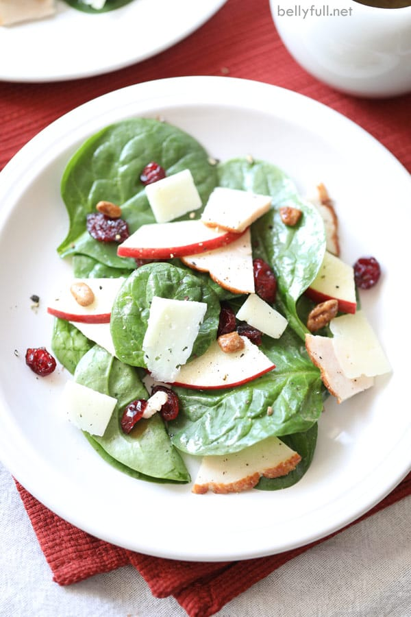 turkey salad with spinach, sliced apple, shaved cheese, and candied pecans on white plate