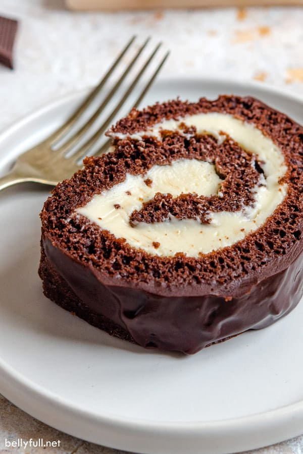 close up slice of swiss roll cake on white plate