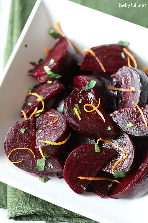 roasted beets with orange and maple glaze with orange zest in white bowl