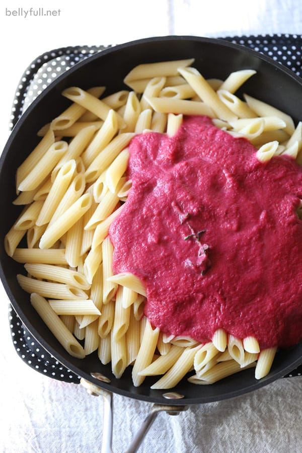 cooked penne pasta in skillet with creamy beet sauce
