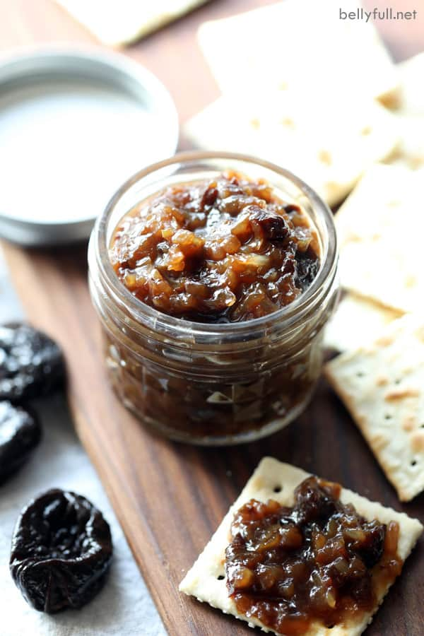 prune onion jam in a glass jar surrounded by crackers