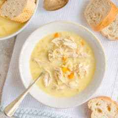 overhead picture of Avgolemono Soup in bowl with spoon and bread