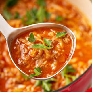 cabbage roll soup in ladle over pot