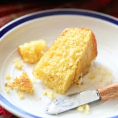 piece of skillet cornbread on white plate with butter knife