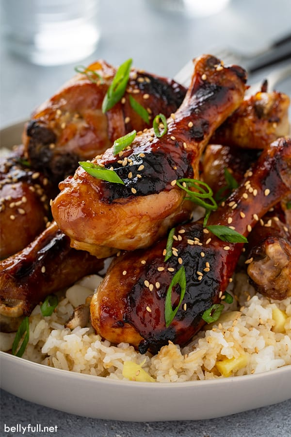 honey soy chicken drumsticks stacked on top of rice in white bowl
