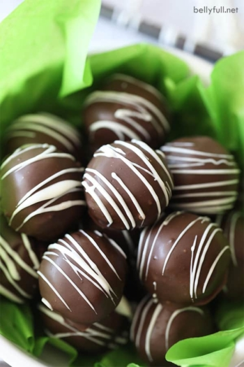 bowl of chocolate Oreo Truffles drizzled with white chocolate with green tissue paper