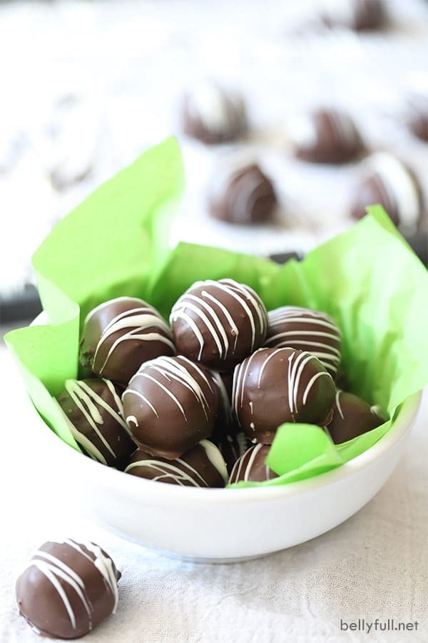 Oreo Truffles in a white bowl with green tissue paper