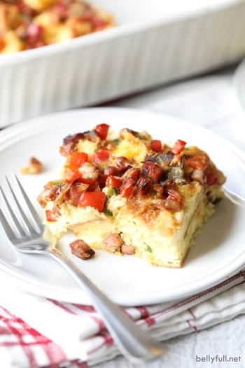 piece of ham breakfast casserole on white plate with fork