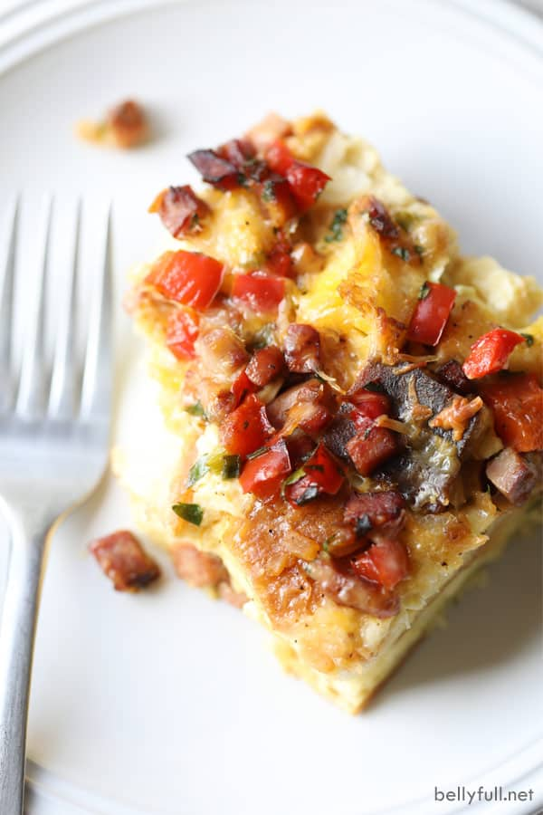 overhead picture of ham breakfast casserole piece on white plate with fork