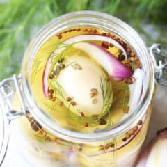 overhead picture of pickled eggs in glass jar with brine
