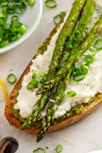 overhead picture of roasted asparagus on toasted bread with pesto and ricotta
