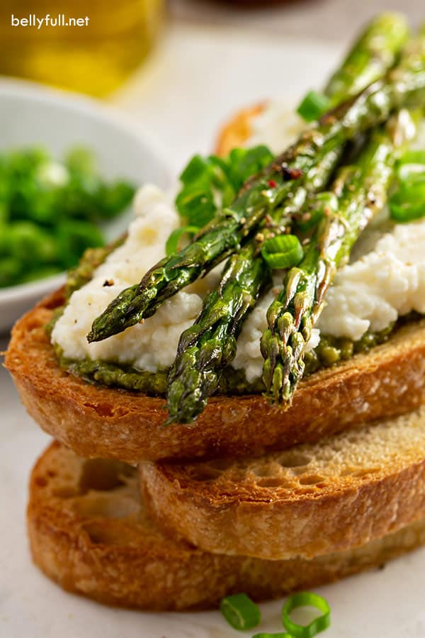 close up picture of roasted asparagus on ricotta and toasted bread