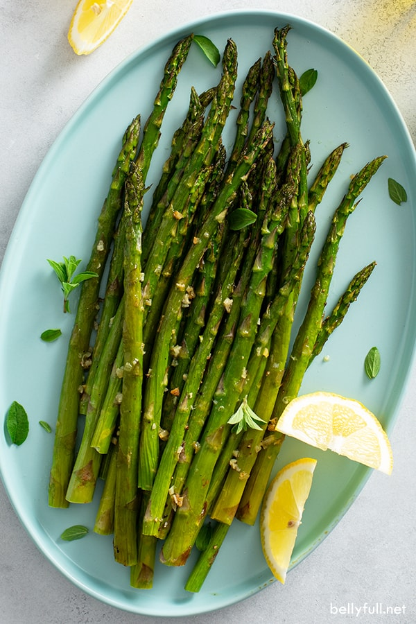 overhead picture of oven roasted asparagus on serving plate with lemon wedges