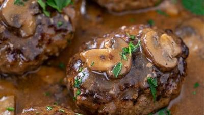sailbury steak in pan smothered with mushroom gravy