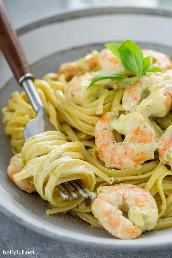 creamy shrimp pesto with pasta wrapped around fork in bowl