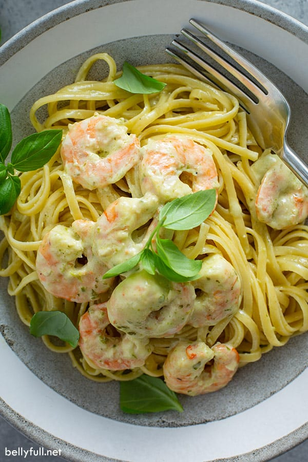 overhead picture of creamy shrimp pesto pasta in bowl with fresh basil and fork