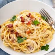 spaghetti carbonara in white bowl with fork