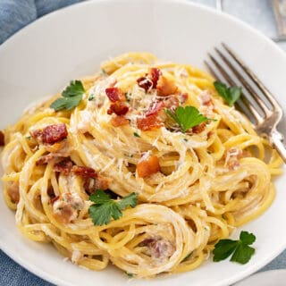 spaghetti carbonara in white bowl with fork