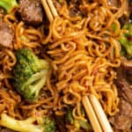 close up picture of homemade beef and broccoli ramen stir fry swirled around chop sticks