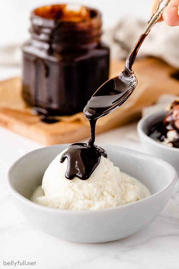 chocolate syrup dripping off of spoon onto vanilla ice cream in white bowl