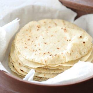 stack of homemade corn tortillas in tortilla warmer