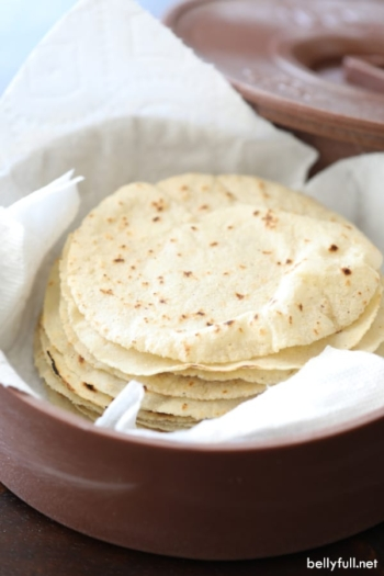 stack of homemade corn tortillas in tortilla warmer