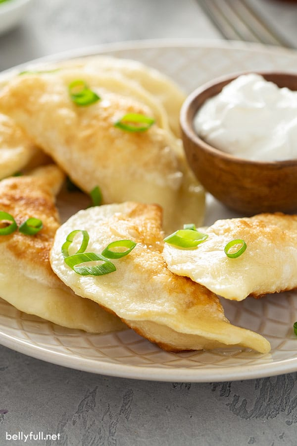 pan fried pierogi on plate with a bowl of sour cream