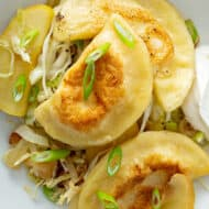 overhead picture of pan fried pierogi on top of sauteed cabbage and apples