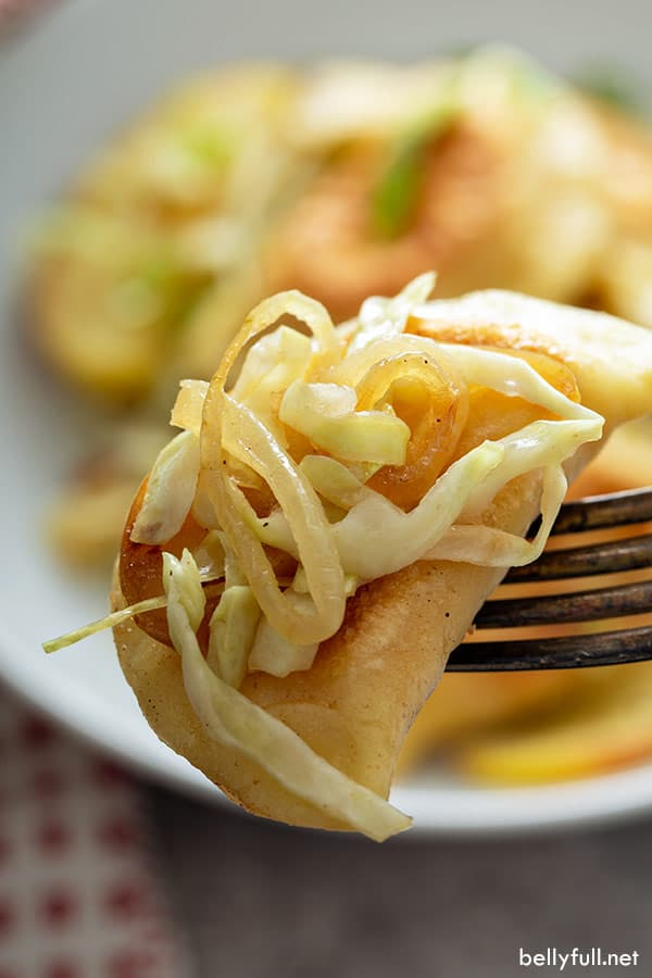 cooked pierogi on fork with sauteed onion and cabbage
