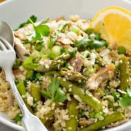 spring vegetable couscous in white bowl with fork