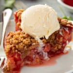 slice of strawberry rhubarb pie with vanilla ice cream on white plate