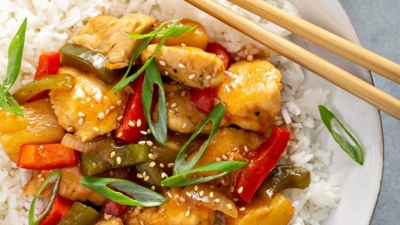 overhead picture of sweet and sour chicken on white plate with chopsticks