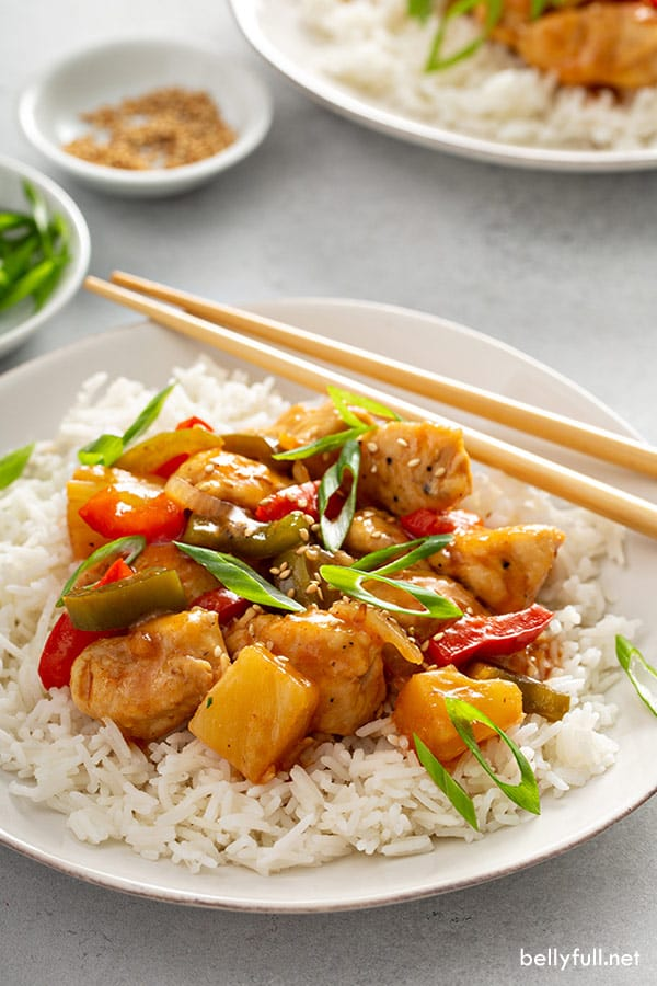 homemade sweet and sour chicken recipe on white plate with chopsticks