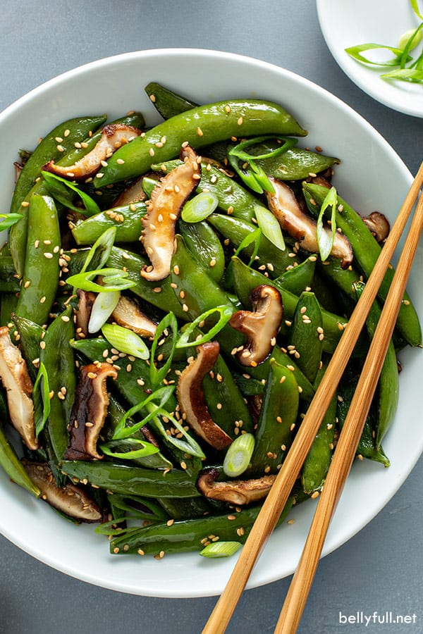 overhead picture of roasted sugar snap peas and mushrooms in white bowl with chopsticks