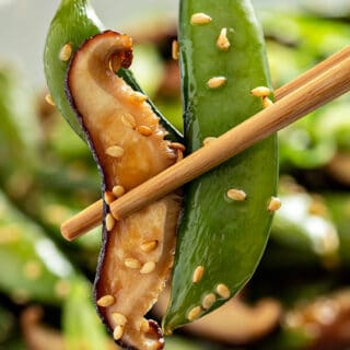 close up picture of roasted shiitake mushroom and snap pea in between two chopsticks