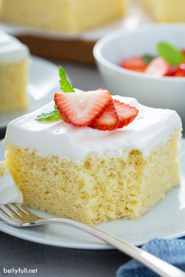 slice of tres leches cake on white plate with fork