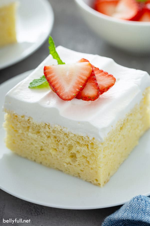 close up picture for a slice of tres leches cake with strawberries