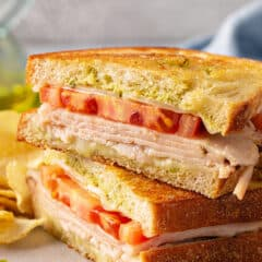 pesto grilled cheese sandwich cut in half and stacked on plate