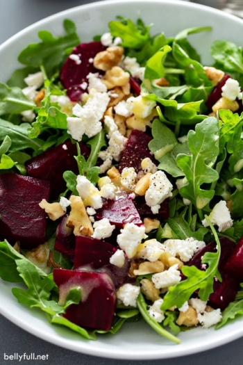 close up picture of baby arugula salad with diced roasted beets, chopped walnuts, and crumbled feta cheese