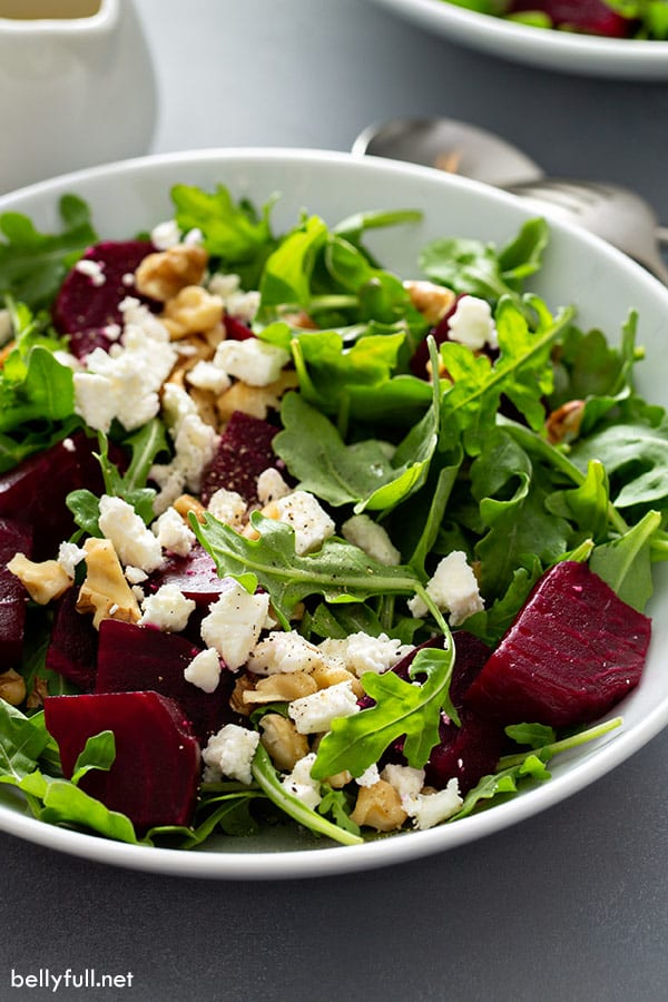 Close up side angle of beet salad with arugula and feta cheese with walnuts