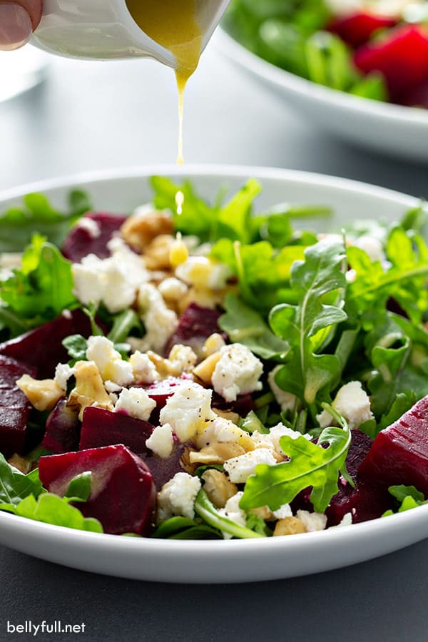 front angle picture of Arugula Beet Salad with vinaigrette dressing being poured on top