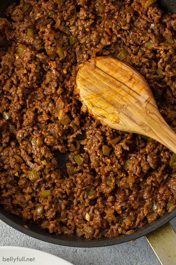 overhead of sloppy joe meat in skillet with wooden spoon