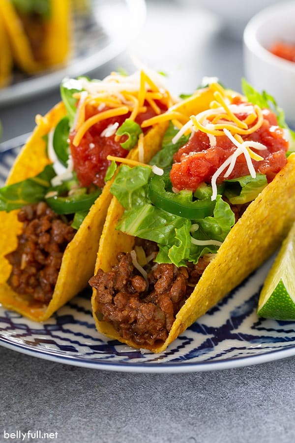 2 crispy tacos on ornate plate topped with lettuce and salsa