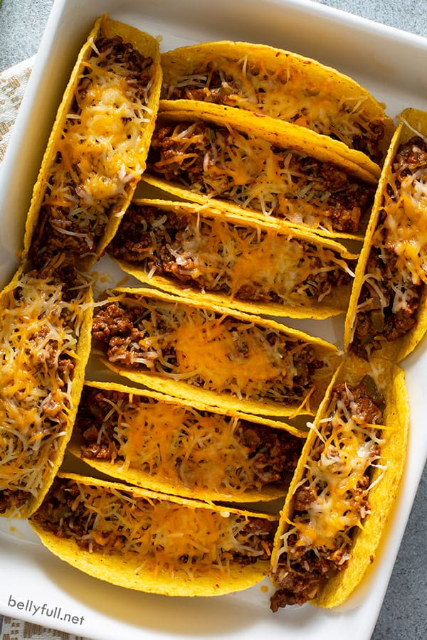 overhead of baked tacos with melted cheese in casserole dish