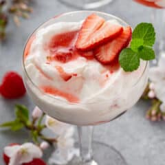 mixed berry fruit fool in parfait glass with sliced strawberries and fresh mint leaves