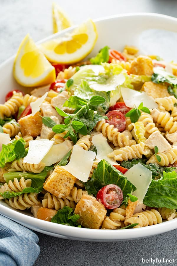 Chicken Caesar Pasta Salad in white serving dish with Parmesan shavings and lemon wedges