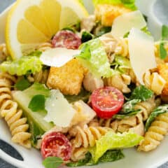 Chicken Caesar Pasta Salad in white dish with a lemon wedge